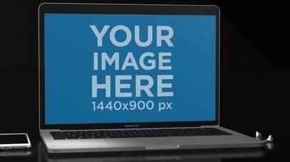 Video of a MacBook Pro Lying on a Flat Dark Surface Near an iPhone and Earpods a15822