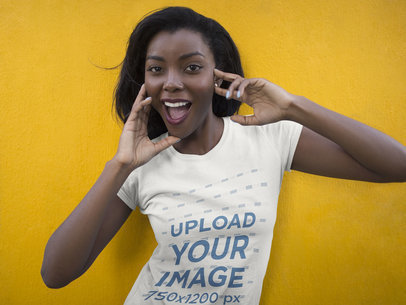Mockup of a Smiling Young Black Girl Wearing a Round Neck Tee While Standing Against a Yellow Wall a16057