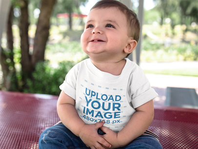 Baby Looking up While Smiling Wearing a Round Neck T-Shirt Mockup a16078