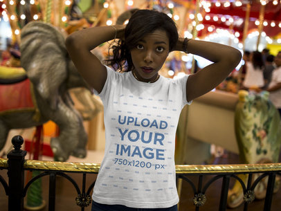 Pretty Black Girl Wearing a Tshirt Mockup While Standing Against a Carousel a16045