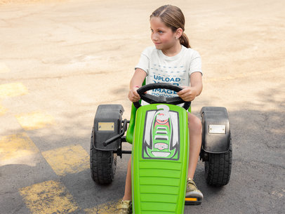 Mockup of a Young Girl Wearing a T-Shirt Mockup While Driving a Green Plastic Go Kart a16152