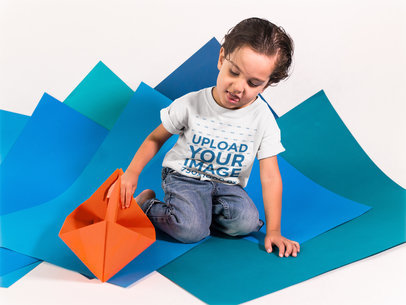 Small Boy Playing with an Orange Paper Boat While Wearing a T-Shirt Mockup a16131