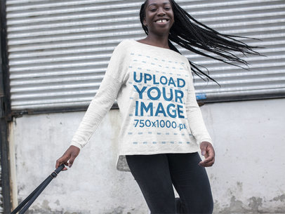 Mockup of a Happy Young Woman with Dreadlocks Wearing a Bella Canvas Long Sleeve Off Shoulder T-Shirt While Walking in an Urban Area a16209