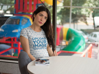 Serious Woman Wearing a Sublimated Tee Mockup While at a Fast Food Resturant a16128