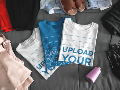 Mockup of Three T-Shirts Lying Folded on a Bed a16939