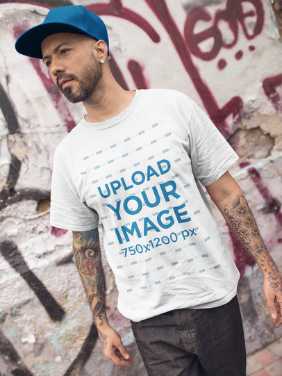 Tattooed Man Walking While Wearing a T-Shirt Mockup in an Urban Area a16983