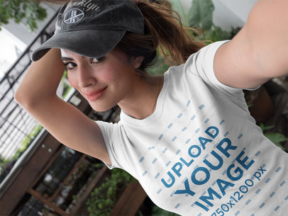 Selfie mockup of a Beautiful Girl Wearing a T-Shirt and a Hat Outdoors a17048