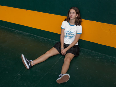 Woman Resting While Sitting Against a Wall Wearing a Ringer T-Shirt Mockup a17063