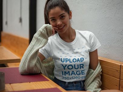 T-Shirt Mockup Being Worn by a Smiling Beautiful Girl in a Coffee Shop a17476