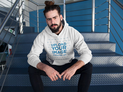 Hipster Man with Beard Wearing a Pullover Hoodie Mockup Sitting on Metal Stairs a17763