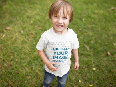 Happy Blonde Boy Wearing a Tshirt Mockup at the Park a17951