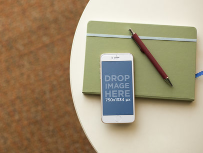 White iPhone 6 Mockup on a Table With a Notebook