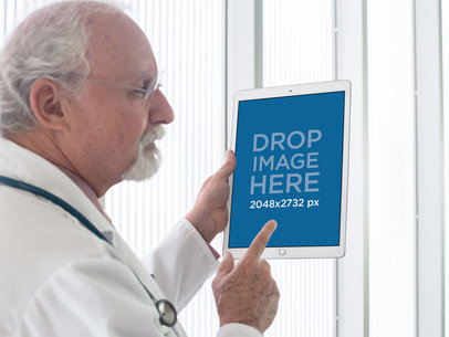 Senior Doctor Holding an iPad Pro at a Hospital Mockup a12440