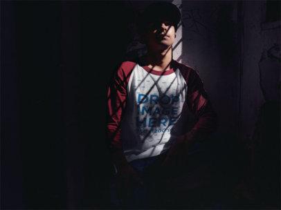 Raglan Tee Mockup of a Young Man Sitting in a Dark Room a12516a
