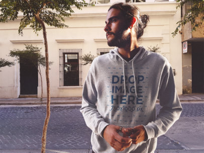 Guy with Long Hair in a Man Bun Wearing a Pullover Heather Hoodie Mockup in the Street b12622