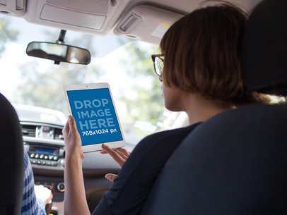 iPad Mini Mockup in Vertical Position Held by a Woman in the Passenger's Seat of a Car While Driving a12943wide