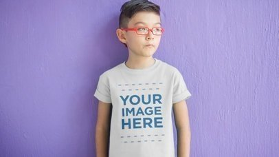Young Asian Boy with Glasses Standing in Front of a Purple Wall Wearing a Kid's Tee Video Mockup a12539