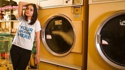 Cinemagraph Mockup of a Young Woman Wearing a T-Shirt Against a Washing Machine at a Laundry a13402