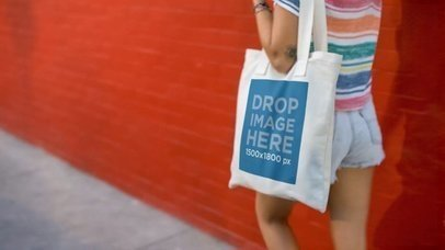 Video Mockup Of A Young Pretty Girl With A Tote Bag Against A Red Wall a13715