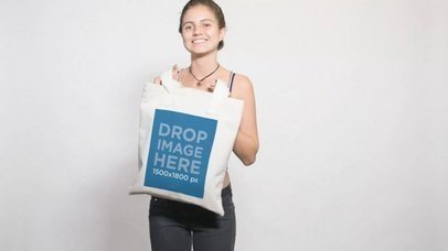 Video Mockup Of A Pretty Girl Wearing a Stripped Tank Top Holding a Tote Bag Against White Background a13714