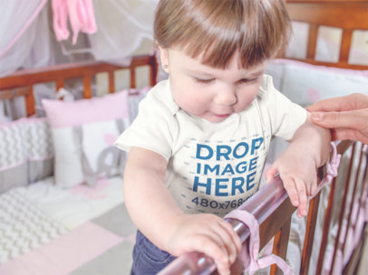 Beautiful Baby Standing On Her Wooden Crib While Wearing A Onesie Mockup a13957