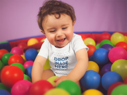 White Baby Wearing A Onesie Smiling While Playing In The Ball Pit Mockup a14026