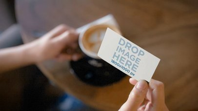 Person Having A Cappuccino At A Cafe While Holding A Business Card Mockup Video a13943b