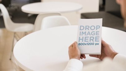 Man Holding a Book in His Hands While Sitting on a White Table Mockup Video a14147