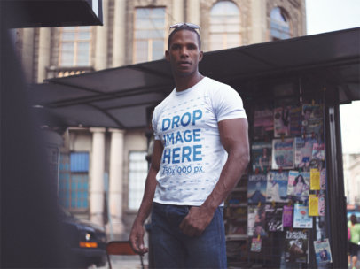 Mockup of a Black Man Wearing a Tshirt While Hanging out in the City near a Newspaper Stand a14221