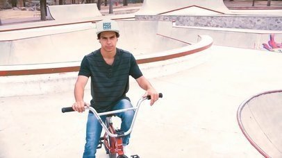 Young Hispanic Man Riding a Bike in a Skatepark While Wearing a Snapback Hat Video Mockup a14189