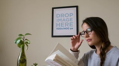 Art Print Framed Mockup in a Living Room With a Beautiful Girl Reading a Book While Wearing Glasses on her Table a14359