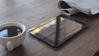 App Demo Video of an iPad Mini on a Wooden Surface Near a Newspaper and a Cup of Coffee a15521