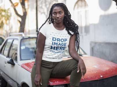 Black Girl Sitting on an Old Car While Wearing a Tee Mockup in the Street a15559