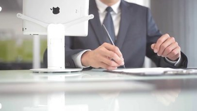 Landscape Position White iPad App Demo Video Standing in an Office While a Businessman is Working on the Back a15614
