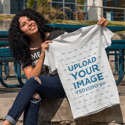Young Curly Haired Girl Showing a T-Shirt Template While Sitting Down Outdoors a15654