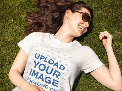 Smiling Woman Lying Down on the Grass While Wearing a Round Neck T-Shirt Template and Sunglasses a15916