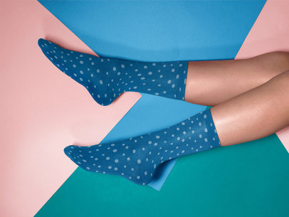 Mockup of a Pair of Socks Being Worn While Lying on a Multicolor Surface a15596