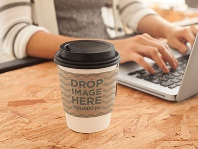 Mockup of a Coffee Cup Sitting Next to a Macbook Pro at an Office a6749