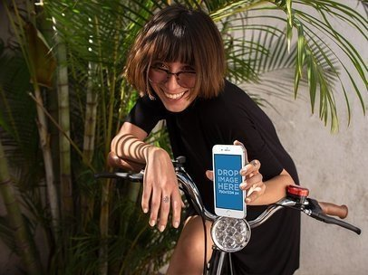 Smiling Young Woman on a Bike Ready to Ride with her White iPhone 7 in Portrait Position Mockup  a12950