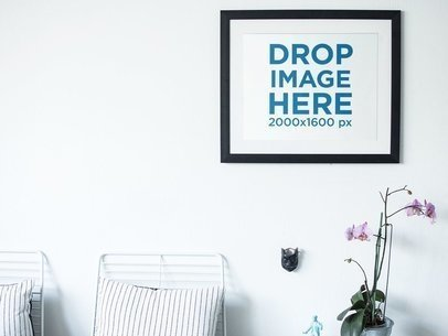 Art Print Mockup Frame on a White Wall Above Some Flowers and Chairs a14777