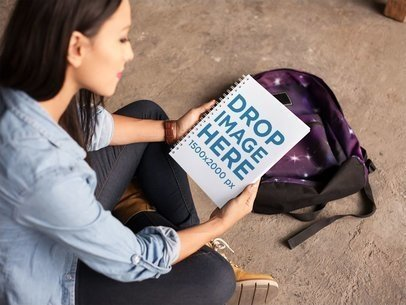 Young Hispanic Girl Looking at a Notebook Template Near Her Backpack a14866