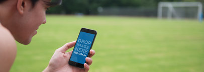 Mockup of a Young Man Using iPhone 6 at Soccer Field a3827