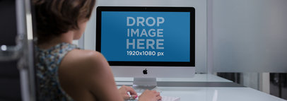 Wide Shot iMac Mockup of a Woman at her Office Desk a12339